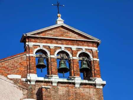 Bells on the church tower with blue sky in the background in Venice