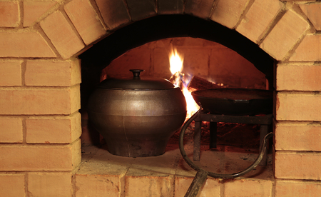 woodfire: Preparing meal in the traditional oven at burning firewood hearth background