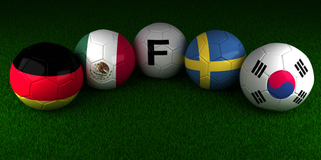 Soccer World Cup 2018 balls with the flag of Group F Germany Mexico Sweden South Korea on the green grass of stadium Banco de Imagens