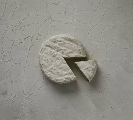 Ripe tasty cheese camembert or brie on a cracked table top view