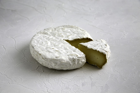 Ripe tasty cheese camembert or brie brie on a cracked table side view
