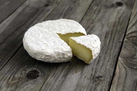 Ripe tasty cheese camembert or brie on an old plank table side view