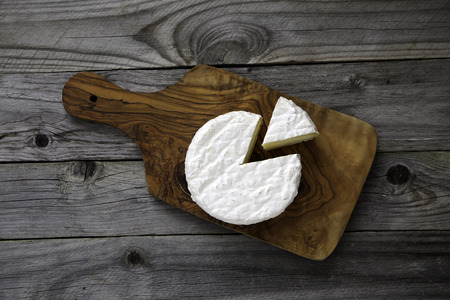 Ripe tasty cheese camembert or brie on a cutting board on an old plank table top view