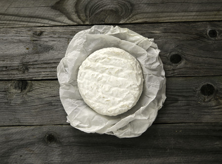 Ripe tasty cheese camembert or brie wrapped in a paper on an old plank table top view