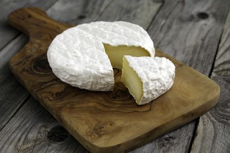Ripe tasty cheese camembert or brie on a cutting board side view