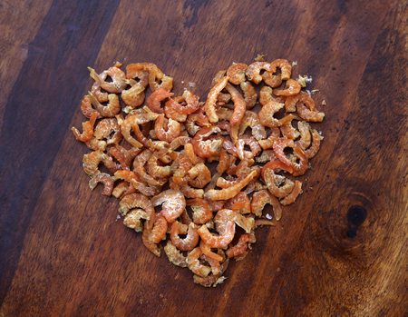 Dried shrimps lie on a wooden table in the shape of a heart. Top view