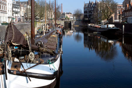 masts: A skyline of vintage buildings and masts of ships in the old district of Delfshaven in Rotterdam, Netherlands.