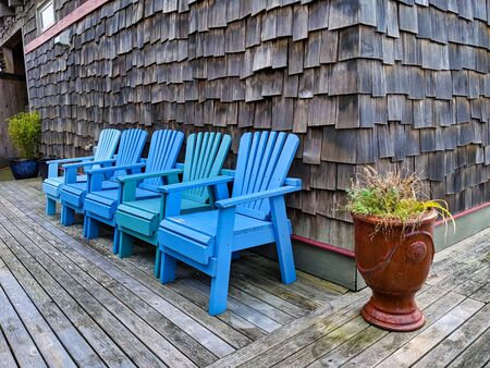 Set of matching blue chairs on a beachfront property patio on a clear day