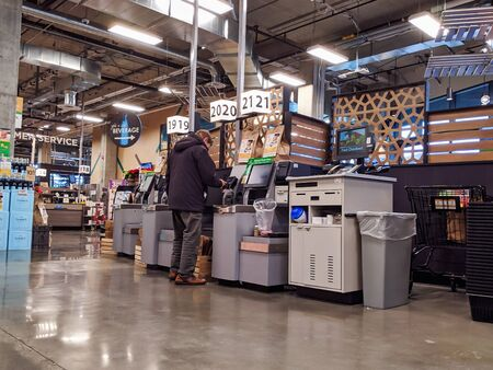 Kirkland, WA / USA - circa December 2019: Self checkout counters being used by customers inside the new QFC grocery store off Central Way.