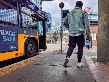 Bellevue, WA / USA - circa December 2019: Man exiting a King County Metro bus at Bellevue Transit Center downtown.