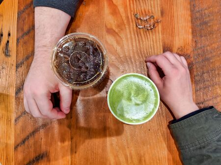 Two people grabbing coffee and tea at a cafe, resting their hands on the table and not touching