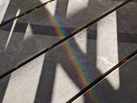 A rainbow cast over harsh black shadows on an outdoor patio on a sunny day