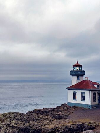 Lime Kiln Lighthouse overlooking a beautiful view of clouds over the water at Friday harbor, Washington