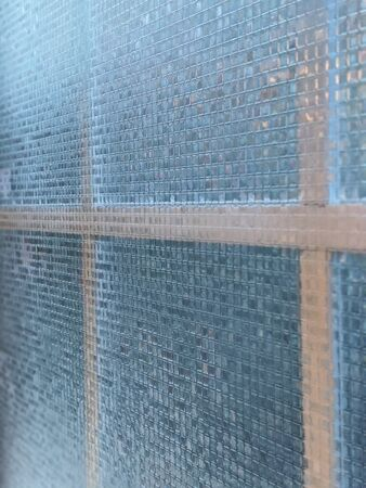 Close up, selective focus on mosaic patterned, removable privacy film on an interior window, to keep people from seeing inside