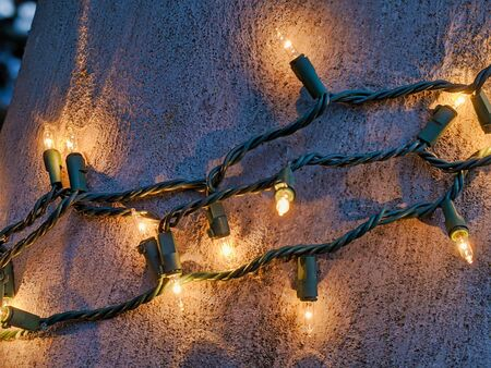 Green and yellow String lights wrapped around a pole outdoors for the holiday season Zdjęcie Seryjne