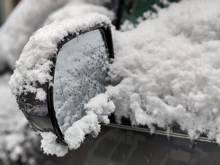 Selective focus on an icy, snow covered car rear view mirror during a snowstorm in the pacific northwest woodlands