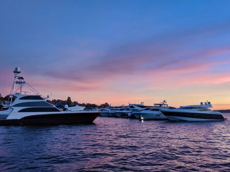 Boats docked on Lake Washington, a stunning vibrant sunset in the sky behind them
