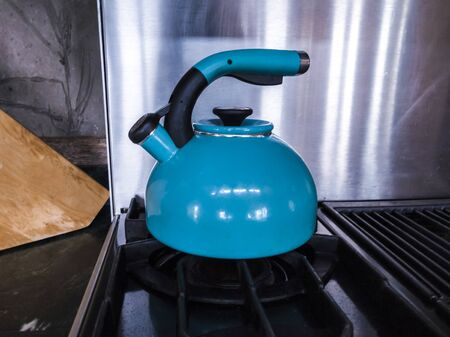 Teal tea kettle boiling hot water on top of a black stove top with a metal backsplash. Stockfoto