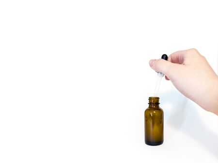 Cannabis extract oil, known as CBD, in an orange tincture bottle with a hand in view, holding the dropper against a white background Reklamní fotografie