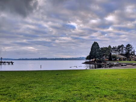View of Lake Washington from the downtown marina beach in Kirkland, WA, clouds hanging over the water 版權商用圖片