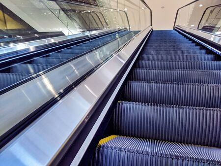 View of empty, yellow lined escalator steps inside a building, leading up to another level