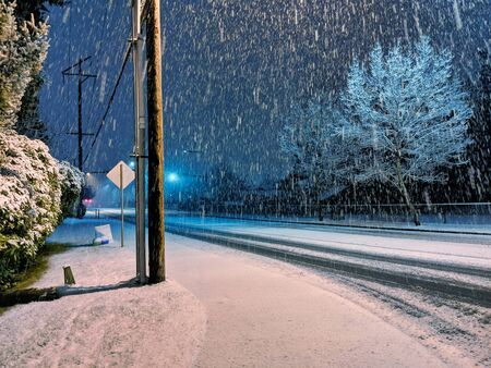 Night view of a winter snow storm starting up in the pacific northwest, wind blowing snow at an angle