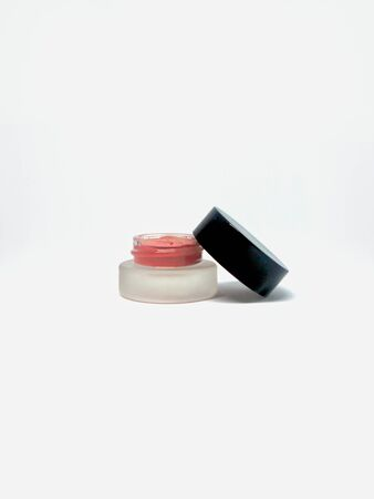 Open, small container of soft pink cheek blush makeup on a white background.