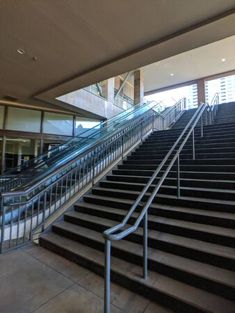 Double staircase with rails leading up to the rooftop of a building in a downtown area Banco de Imagens
