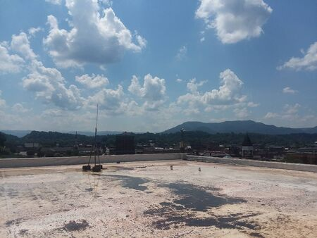 View of a small mountainous city from a building rooftop, big fluffy clouds dotting the sky Stock fotó