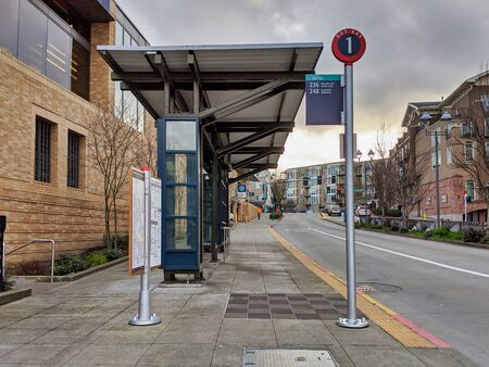 Kirkland, WA  USA - circa January 2020: Exterior view of a bus bay at the downtown Kirkland Transit Center near the King County Library and parking garage 報道画像
