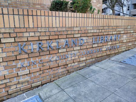 Kirkland, WA  USA - circa January 2020: Exterior view of the King County Kirkland Library sign on a low brick wall.