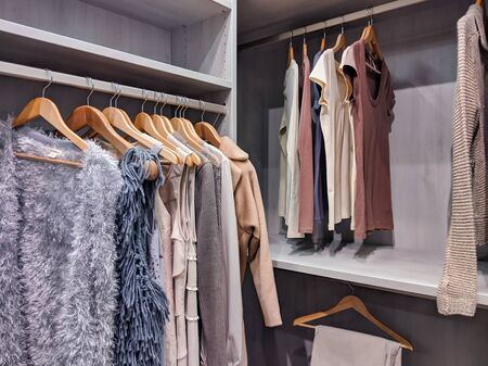 A well stocked walk in closet with all clothing and shoes organized within Stock Photo