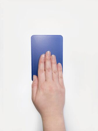 Flat lay view of a hand on top of a single blue tarot card