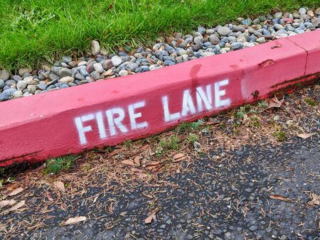 Downward angle of a bright red fire lane sign on a curb in a suburban neighborhood