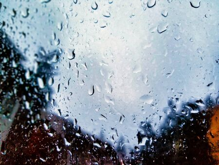Selective focus on rain drops dotting across a car door window, blurring out the background behind it