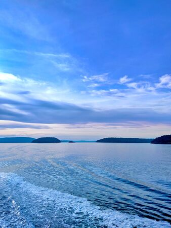 Waves quaking behind a ferry making its way through the San Juan Islands in the pacific northwest. Stock Photo