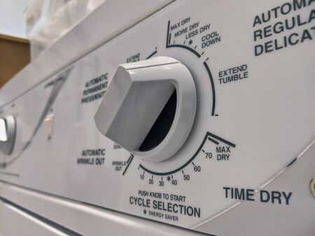Close up of a knob on a clothing dryer control panel