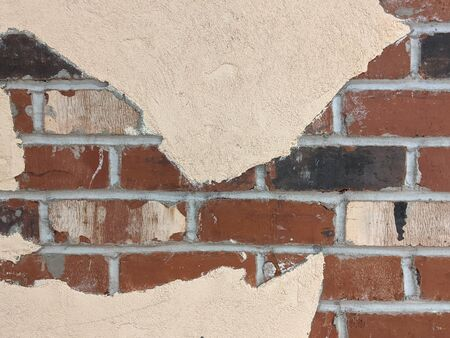 Close up of the texture on an exposed, red brick wall peeking out behind a tan paint job Standard-Bild