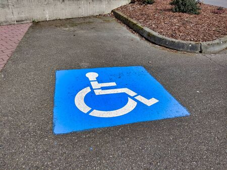 View of a blue handicapped parking paint marker in a parking lot outdoors Foto de archivo
