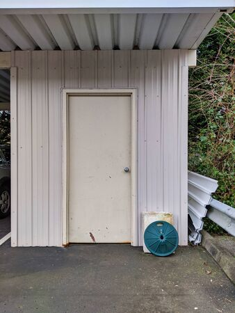 Front view of a small, white shed in a backyard garage area, storing gardening and other outdoor tools