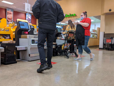 Kirkland, WA / USA - circa March 2020: Signs instructing social distancing at the self checkout lines at a Safeway grocery store during the shelter in place order in Washington Editorial