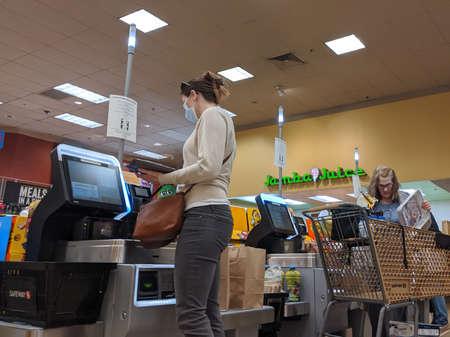 Kirkland, WA / USA - circa April 2020: Customers wearing face masks while doing self checkout during the COVID-19 coronavirus outbreak.