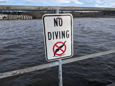 Close up of a No Diving sign at Lake Washington on a sunny, somewhat cloudy day