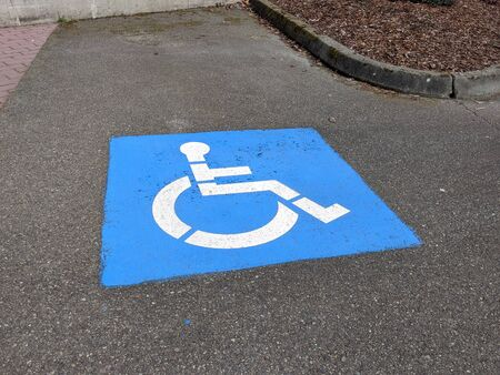 High angle view of a handicap icon at a parking spot in a paved lot outdoors