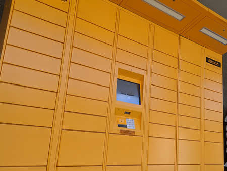 Kirkland, WA / USA - circa May 2020: Street view of a set of bright yellow Amazon parcel lockers outside of a grocery store.