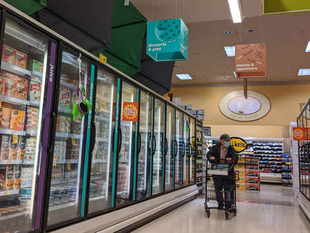 Kirkland, WA / USA - circa March 2020: Elderly man in the freezer food aisle amidst the COVID-19 pandemic.