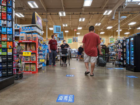 Kirkland, WA / USA - circa April 2020: Customers with face masks on shopping in a Fred Meyer grocery store, with social distancing stickers on the floor for safety