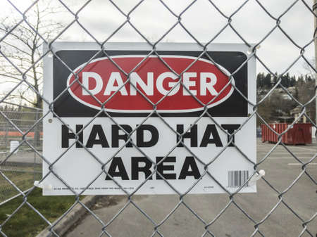 Seattle, WA / USA - circa March 2020: View of a Danger - Hard Hat Area sign on a chain link fence outside a construction zone.