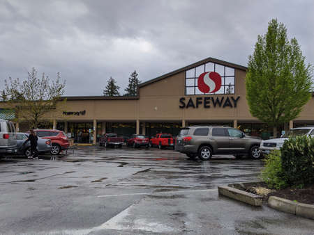 Bellevue, WA / USA - circa April 2020: Street view of a Safeway grocery store with people approaching the entrance to shop for food.