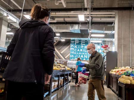 Seattle, WA / USA - circa May 2020: Elderly man wearing a face mask while grocery shopping inside a QFC grocery store.